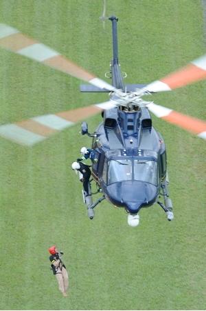 O helicóptero Bell 412 da DSP paira sobre um campo verde, enquanto os tripulantes içam soldados para dentro da aeronave. Foto Greg L. Davis www.focalplaneimagery.com